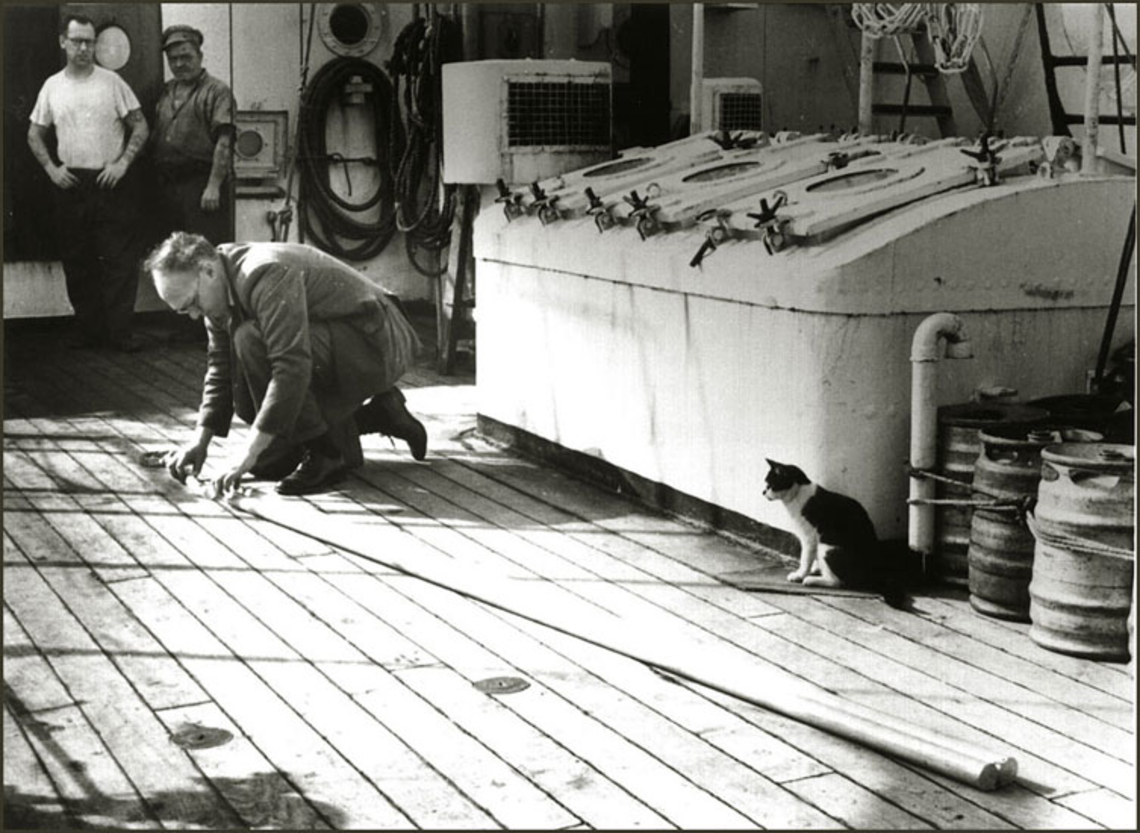 John Swallow assembling an early float on RRS Discovery II, watched intently by two matelots and the ship's cat.